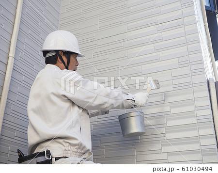 戸建て住宅の外壁を塗る塗装職人 61030494