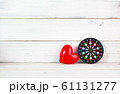 Red Heart Shaped with Dartboard over white wood 61131277