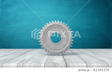 3d rendering of light-grey metal gearwheel standing on wooden surface on blue wall background. 61165370