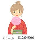 わたあめを持つ赤い浴衣の若い女性(お団子ヘア) 61264590