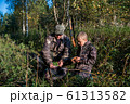 Two hunters father and son are eating together in the forest. Bushcraft, hunting and people concept 61313582