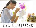 花に水をやる女性 61362481