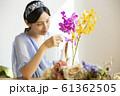 花に水をやる女性 61362505