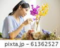 花に水をやる女性 61362527