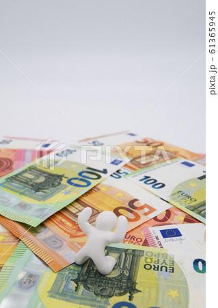 ユーロ札の上に乗って喜ぶ人 縦位置 白背景 61365945