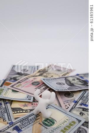 ドル札の上に乗って喜ぶ人 縦位置 白背景 61365961