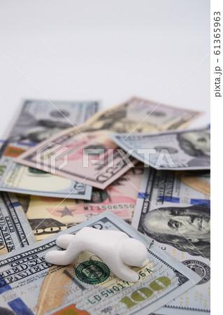ドル札の上に乗って落ち込む人 縦位置 白背景 61365963