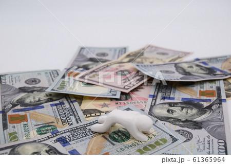 ドル札の上に乗って落ち込む人 横位置 白背景 61365964
