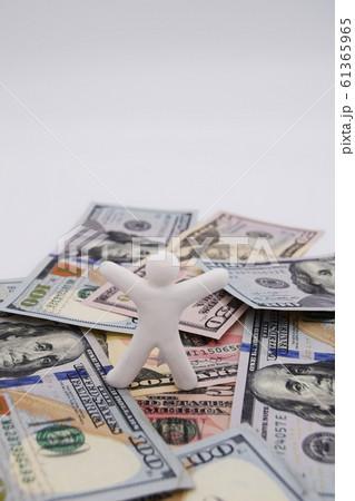 ドル札の上に乗って喜ぶ人 縦位置 白背景 61365965