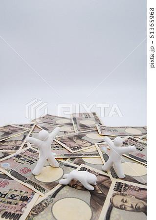 1万円札の上に乗って喜んでいる人 何もなく落ち込んでいる人 縦位置 白背景 61365968