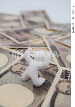 1万円札の上に乗って喜ぶ人 縦位置 白背景 61365970