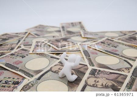 1万円札の上に乗って喜ぶ人 横位置 白背景 61365971