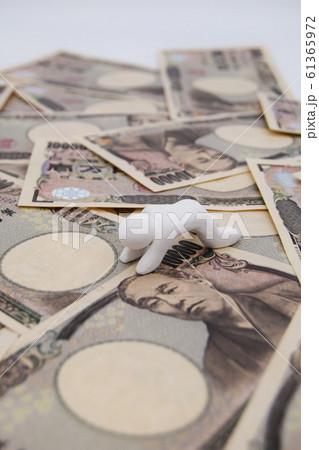 1万円札の上に乗って落ち込む人 縦位置 白背景 61365972