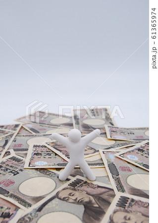 1万円札の上に乗って喜ぶ人 縦位置 白背景 61365974