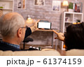 Back view of elderly retired couple looking at a smartphone with white isolated screen 61374159
