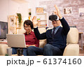 Old elderly retired man using VR virtual reality headset in their cozy apartment 61374160