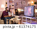 Man sitting on couch and playing video games on television 61374175