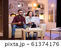 Young couple having a good time while playing video games on television 61374176