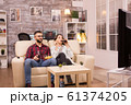 Cheerful young couple sitting on sofa and watching a movie on tv 61374205