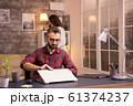 Bearded entrepreneur opening laptop to start working from home 61374237