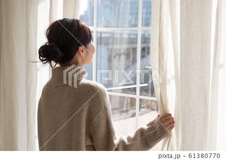 カーテンを開ける女性 61380770