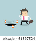 Businessman is talking on the phone without being careful of the hole on the ground. 61397524