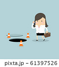 Businesswoman is talking on the phone without being careful of the hole on the ground. 61397526