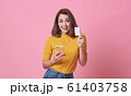young woman holding mobile phone and credit card 61403758