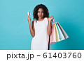 Young woman showing credit card and shopping bags 61403760
