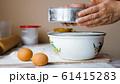 Mature woman is adding a flour through sieve in steel bowl for preparing a dough 61415283