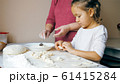 Grandmother with granddaughter is making dumplings with cheese at home kitchen 61415284