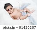 Newborn infant baby boy lying on a white blanket. He is wearing sunglasses. 61420267