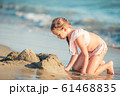 Little adorable girl playing on beach with ball 61468835