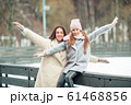 Little adorable girl with her mother skating on ice-rink 61468856