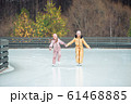 Adorable girls skating on ice rink outdoors in winter snow day 61468885