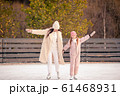 Little adorable girl with her mother skating on ice-rink 61468931