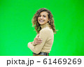 Happy young woman with a cute smile standing on green background with copy space. 61469269