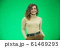 Glowing girl posing on green background, looking positive, smiling. 61469293