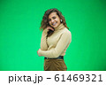 Portrait of gorgeous female model posing in white fashion clothes in studio over green background. 61469321