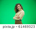 Portrait of gorgeous female model posing in white fashion clothes in studio over green background. 61469323
