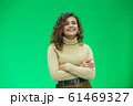 Beautiful woman with kinky hair in beige clothes, isolated on green, looking pleased. 61469327
