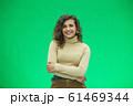 Portrait of a beautiful friendly african american woman with curly hairstyle and lovely smile isolated on a green background, her hands folded. 61469344