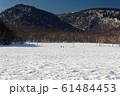 残雪の尾瀬ヶ原を行く登山者 61484453