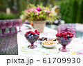 Beautiful glasses of colored purple glass on the table with berries and flowers 61709930