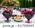 Beautiful glasses of colored purple glass on the table with berries and flowers 61709945