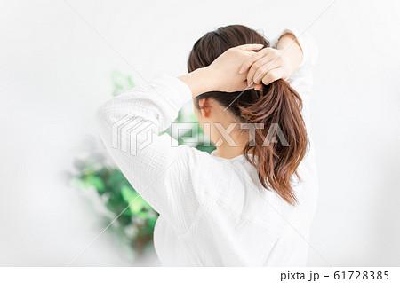 髪を縛る女性 61728385