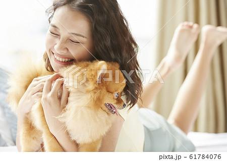 小型犬と暮らす若い女性 61784076