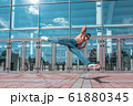 man in a jump on twine, muscular torso, dancer, young guy, city summer, dancing street dances, modern style youth. Fashion fitness sport motivation. Free space copy text. Background glass doors. 61880345