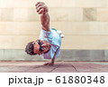 man in flight, stands on one arm, Superman pose, young guy dancer, in summer in city, dancing street dances, modern youth style. Fashion and fitness sport. T-shirt glasses. Free space for copy text. 61880348