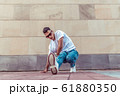Male dancer young guy, in summer in the city, dancing street dances, modern youth style. Fashion and fitness sport. T-shirt glasses and jeans sneakers. Free space for copy text. 61880350